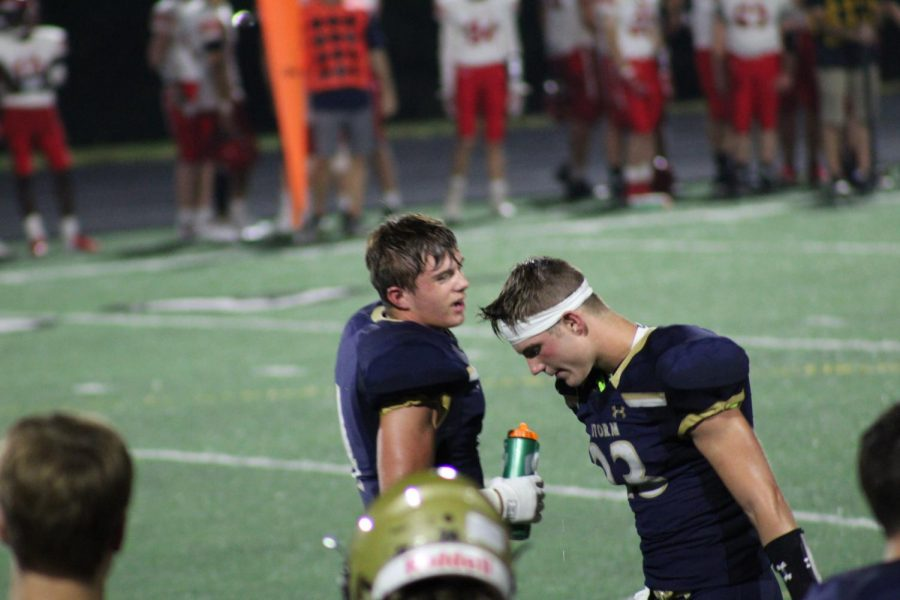 Captains Cooper Jewett (Left) and Jason Carlos (Right) quickly communicate between plays during the Elkhorn v. Elkhorn South game on Aug. 31st.