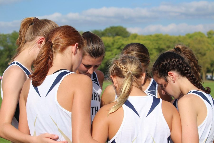 In this together: Varsity girls' cross country huddles up before a run.  The team supports each other on and off the course, as they help motivate each other.